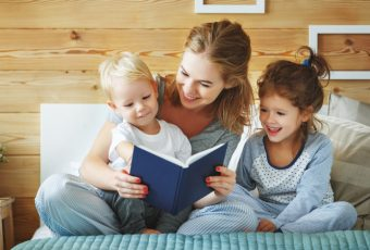 Family Mother Reading To Children Book In Bed