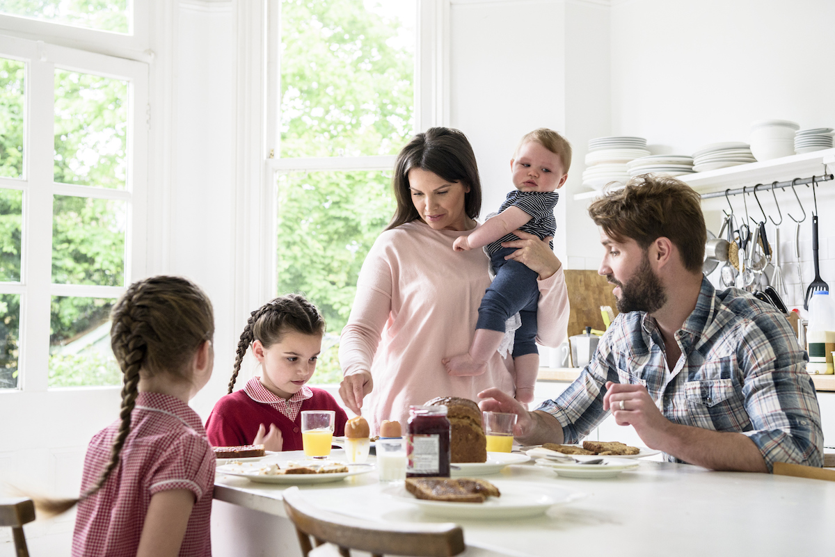 Family Sitting At Breakfast Table, Mother Holding Baby Boy, Father And Girls Eating Food